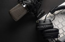 Flat lay, Studio microphone with professional headphones on a PC keyboard. Black on a black background. Podcasts, radio, streams, blogging, working with sound, recording tracks